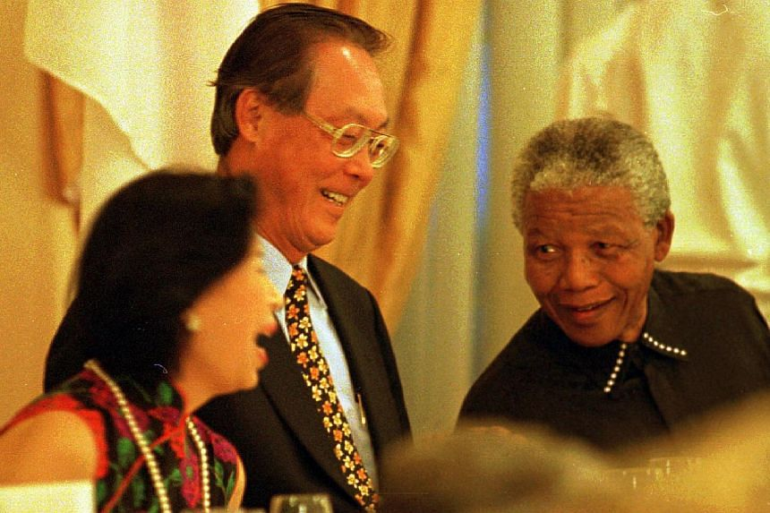 """South African President Nelson Mandela sharing a light moment with then Prime Minister Goh Chok Tong and his wife at a banquet dinner on Feb 25, 1997. Emeritus Senior Minister Goh paid tribute to Mr Mandela, saying he was """"saddened by the passi"""
