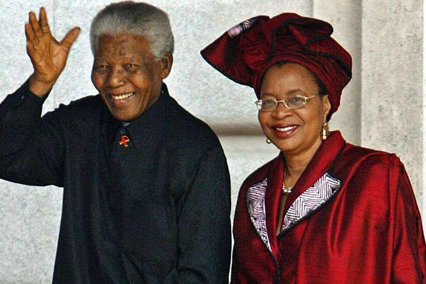 Former South African President Nelson Mandela and his wife Graca Machel smiling to photographers as they arrive at Madrid's Almudena Cathedral to attend the Spanish Crown Prince's wedding, May 22, 2004. South Africa's President Jacob Zuma said, Thurs