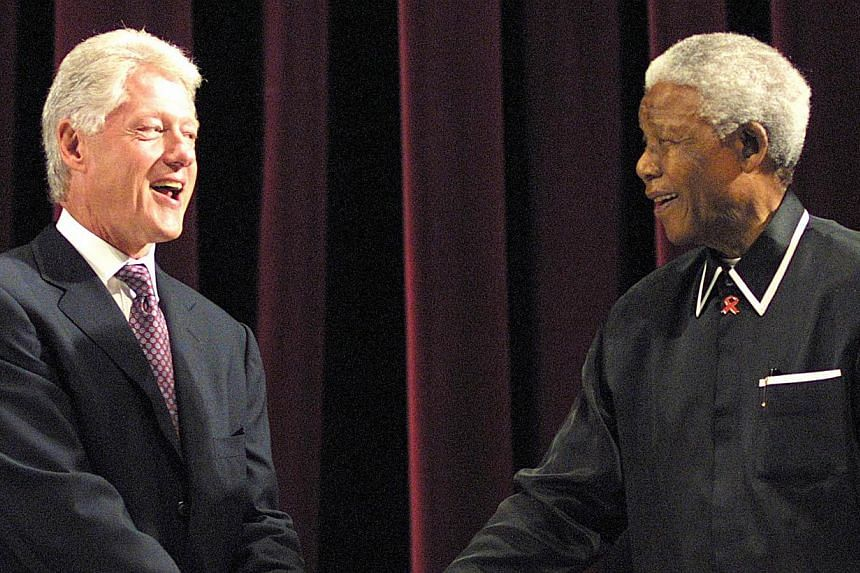 Former US President Bill Clinton (left) shakes hands with former South African President Nelson Mandela during the inaugural Annual Nelson Mandela Lecture at the Johannesburg Civic Centre, July 19, 2003. The lecture coincided with Mandela's 85th birt