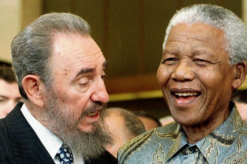 Cuban leader Fidel Castro (left) shares a laugh with then South Africa President Nelson Mandela at a meeting of the World Trade Organization in Geneva, Switzerland, May 19, 1998. South Africa's president Jacob Zuma says, Thursday, Dec 5, 2013, that M