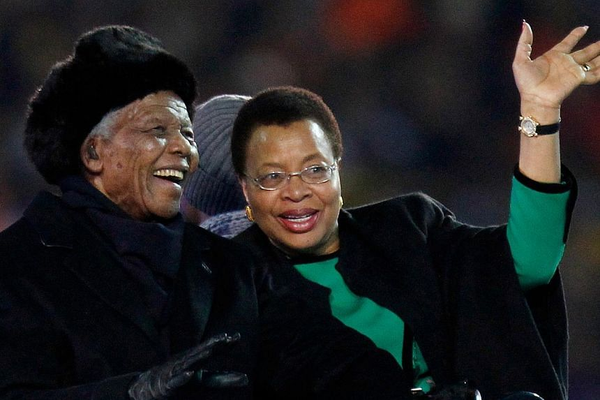 Former South African President Nelson Mandela (left) sits next to his wife, Graca Machel, as they are driven across the field ahead of the World Cup final soccer match between the Netherlands and Spain at Soccer City in Johannesburg, South Africa, Ju