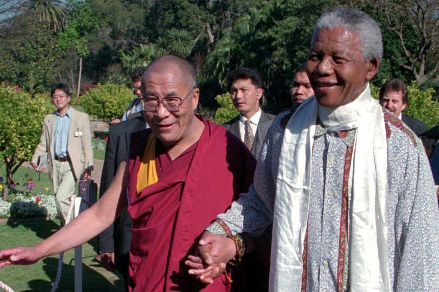 The Dalai Lama (left) walks hand-in-hand with South African President Nelson Mandela prior to an official reception at the presidential office in Cape Town, South Africa, on Aug 22, 1996. The Dalai Lama said on Dec 6, 2013, in a letter sent to the fa