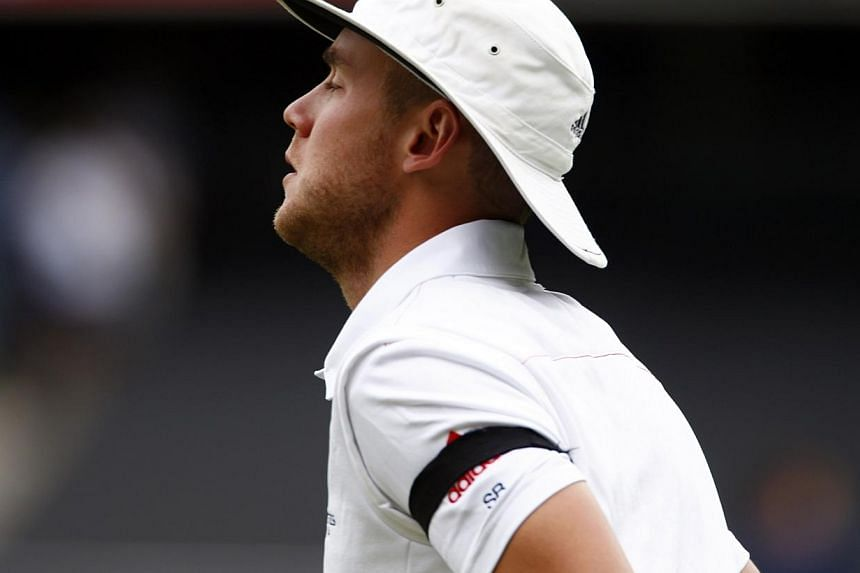 England's Stuart Broad runs onto the ground wearing a black armband as the players prepare to observe a minute of silence to commemorate former South African President Nelson Mandela's death before starting the second day's play in their second Ashes