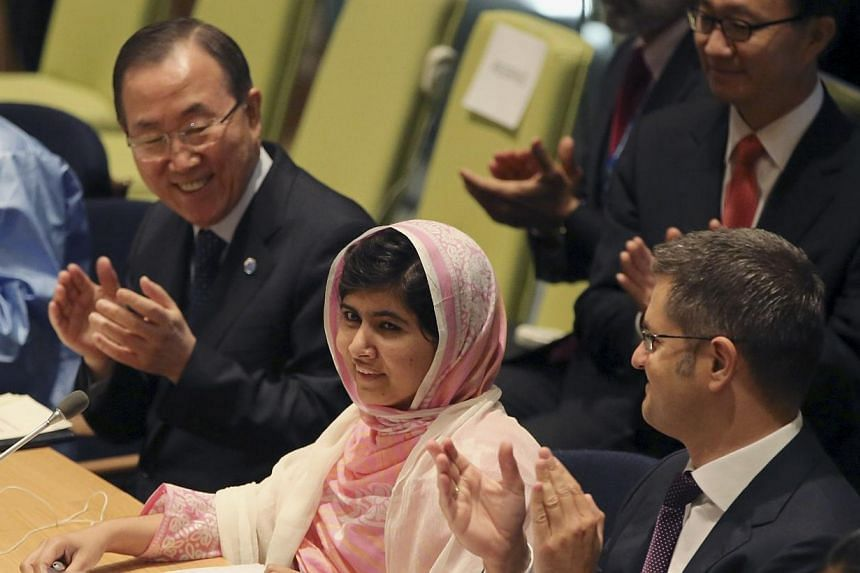 United Nations Secretary-General Ban Ki-moon (left) applauds as the members of the 'Malala Day' Youth Assembly wish Malala Yousafzai (centre) a happy birthday, on Friday, July 12, 2013 at United Nations headquarters.Pakistani schoolgirl Mal