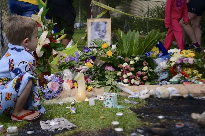 A boy pauses at a shrine outside the home of former South African President Nelson Mandela in Johannesburg, on Dec 6, 2013. South Africans woke on Friday, Dec 6, 2013, to a future without Nelson Mandela, and some said they feared the anti-apartheid h