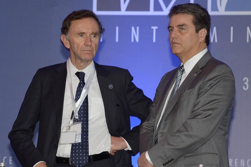 World Trade Organization (WTO) General Director Roberto Azevedo (right) stands next to British Trade Minister Stephen Green (left) prior to the Yemen's Acession ceremony in the 9th WTO Ministerial Conference in Nusa Dua, on December 4, 2013. The head