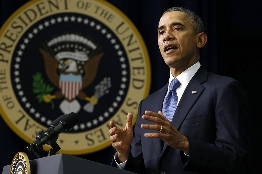 US President Barack Obama pauses while speaking at the White House Youth Summit on the Affordable Care Act in Washington on Dec 4, 2013. Mr Obama said on Thursday he intends to propose National Security Agency reforms to reassure Americans that their