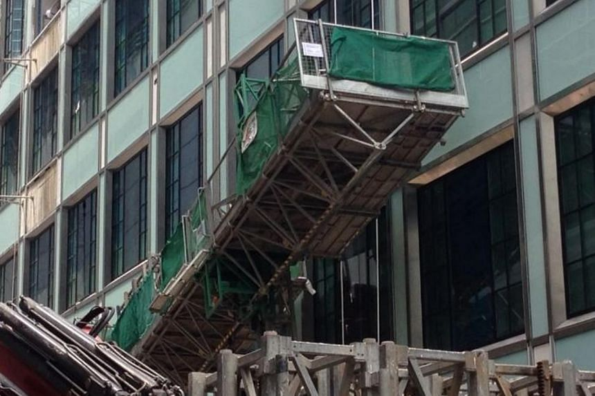 Rescuers from the Singapore Civil Defence Force (SCDF) on Saturday responded to an incident at Boon Tat Link behind SGX Centre, where an industrial elevator carrying four workers was believed to have tilted to one side. -- ST PHOTO: YEO SAM JO