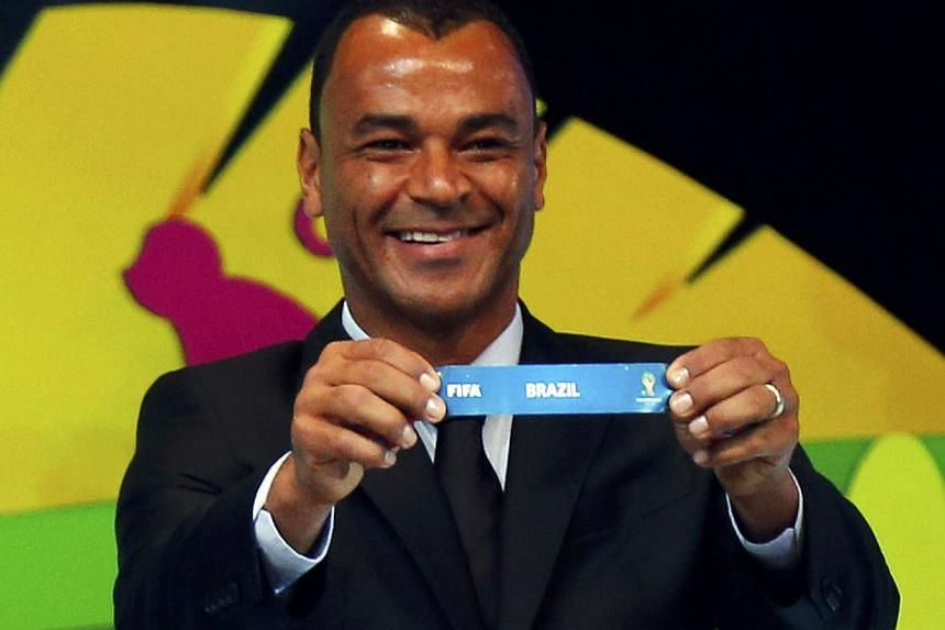 "Former Brazil soccer player Cafu holds the slip showing ""Brazil"" during the draw for the 2014 World Cup at the Costa do Sauipe resort in Sao Joao da Mata, Bahia state, Dec 6, 2013. The world Cup hosts might not admit it but they will already have one"