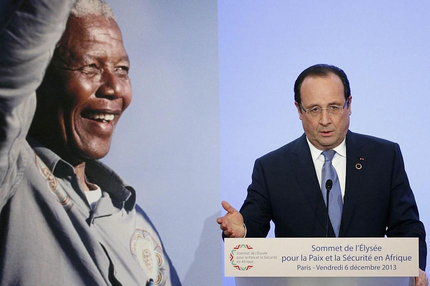 French President Francois Hollande delivers a speech during the Summit for Peace and Security in Africa at the Elysee Palace in Paris next to a portrait of late South African President Nelson Mandela. Mr Hollande urged African leaders on Friday