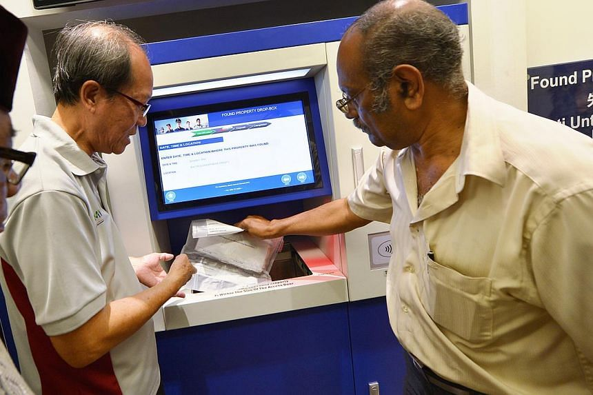 Mr Haron Hashim (left), 63, Mr Govindasamy (right), 66, and Mr Thomas Lim (centre), 60, demonstrate how to use the Found Property Drop-box that is installed in the new Neighbourhood Police Post at West Coast on Dec 3, 2013. -- PHOTO: ALPHONSUS CHERN