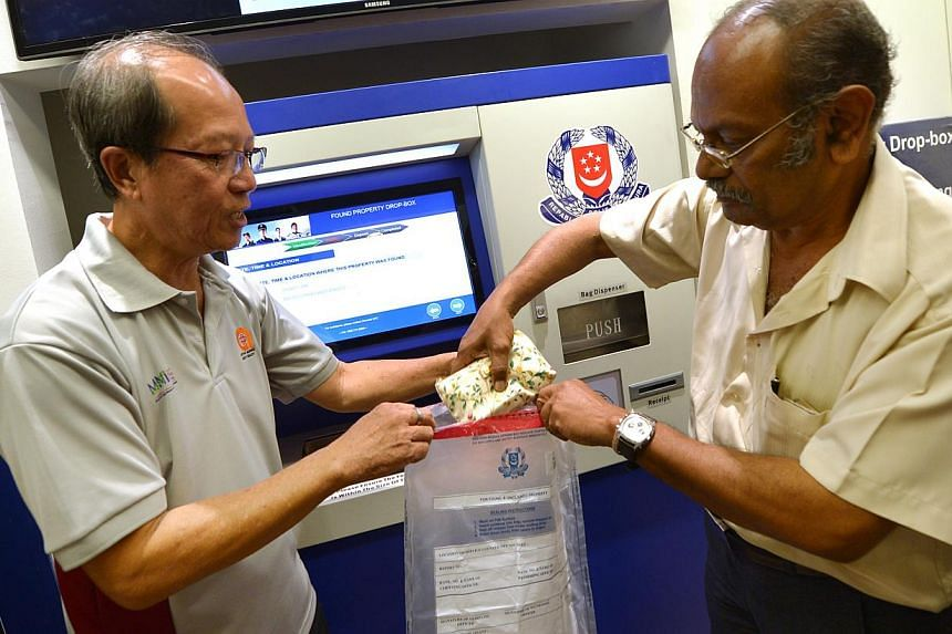 Mr Govindasamy (right), 66, and Mr Thomas Lim (left), 60, demonstrate how to use the Found Property Drop-box that is installed in the new Neighbourhood Police Post at West Coast on Dec 3, 2013. -- PHOTO: ALPHONSUS CHERN