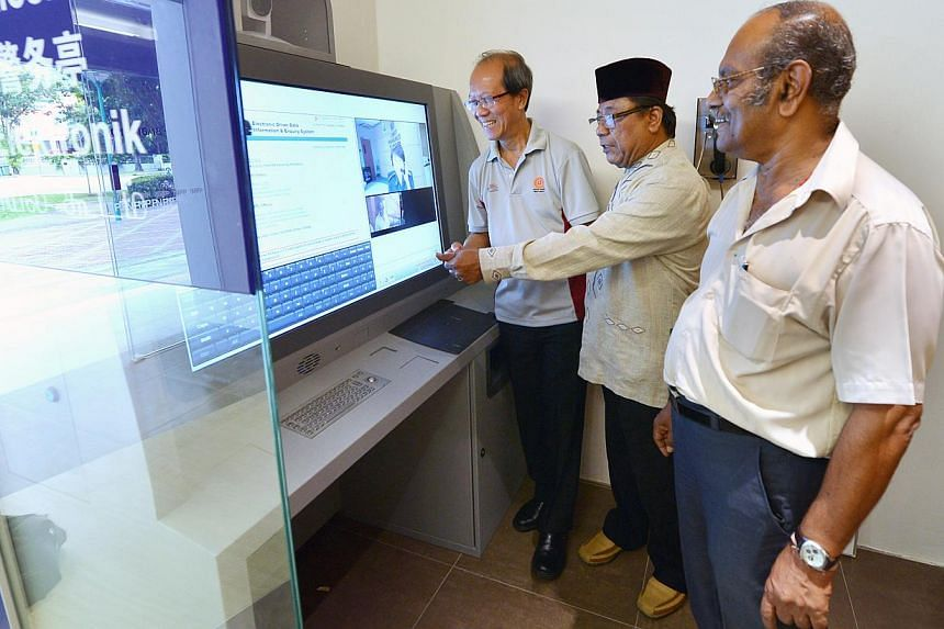 Mr Haron Hashim (centre), 63, Mr Govindasamy (right), 66, and Mr Thomas Lim (left), 60, demonstrate how to use the e-kiosk installed in the new Neighbourhood Police Post at West Coast on Dec 3, 2013. -- PHOTO: ALPHONSUS CHERN