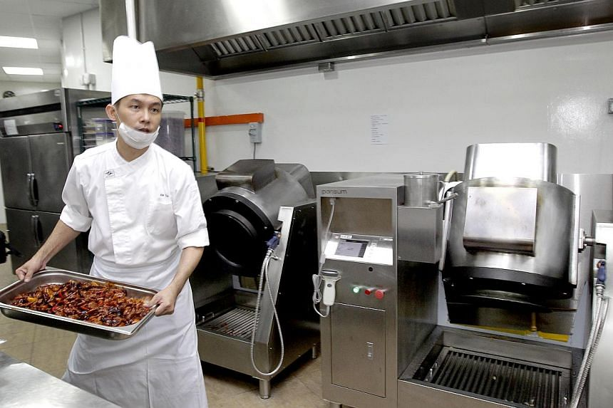 Chef Alan Teo, 39, finishes cooking his dishes using the Cooking Machines behind him at Tung Lok on Dec 6, 2013. -- ST PHOTO: CHEW SENG KIM