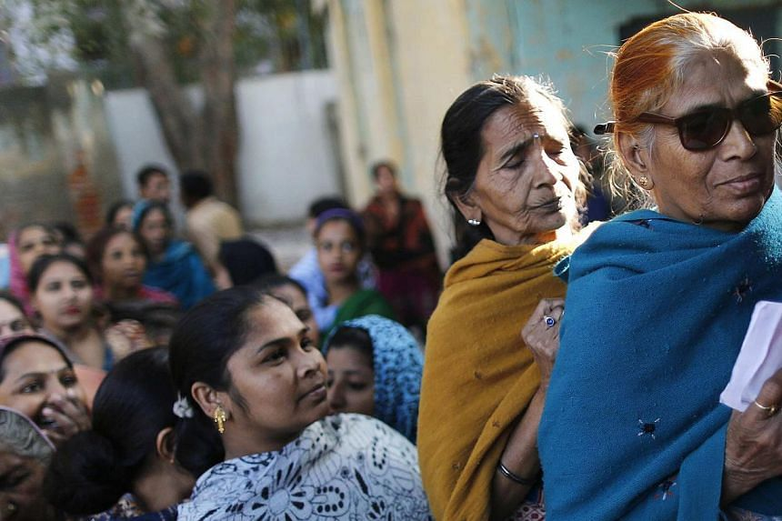 Voters line up in a queue outside a polling booth to cast their vote during the state assembly election in Delhi on Dec 4, 2013. Vote counting began in four Indian states on Sunday where the nationalist opposition was in line to wrest power from the