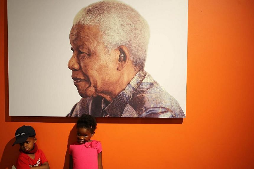 Two children pose in front of a poster of South African former president Nelson Mandela at the Nelson Mandela Foundation's Centre of Memory in Houghton, Johannesburg, on Dec 7, 2013, two days after Mandela's death.Mr Nelson Mandela's family s