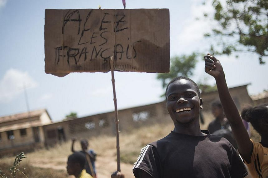 """A man holding a placard that reads """"Go France"""" as people from Bouar welcome the French military arriving from Cameroon on Dec 7, 2013. The troops received a triumphant welcome as they deployed in strife-torn Central African Republic, while the Africa"""