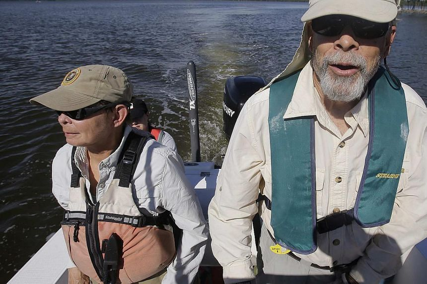 Search volunteers Donna Buckley (left) and her husband John Buckley pilot their vessel near a location where a pod of pilot whales were stranded in the Everglades National Park, on the southwestern Florida coast on Dec 5, 2013. Rescuers involved in t
