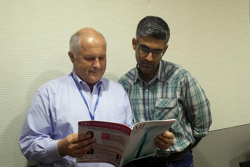 Mr Kouk (left) is listed as the paper's main author. (Below) Prof Ostbye (left) and Prof Malhotra looking at a copy of the Singapore Medical Journal.