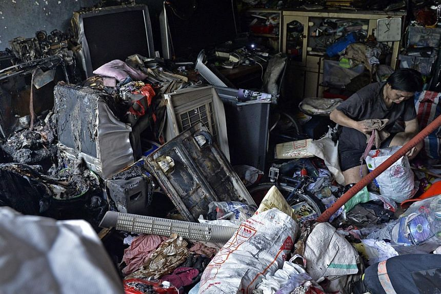 Mr Eason Ho (above), 34, and his brother Cheng Hock, 33, at their flat to salvage items and clean it up. -- ST PHOTOS: DESMOND FOO, MARK CHEONG