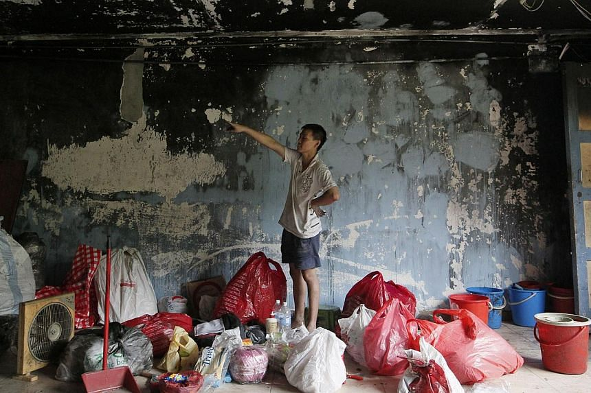 Mr Eason Ho, 34, and his brother Cheng Hock (above), 33, at their flat to salvage items and clean it up. -- ST PHOTOS: DESMOND FOO, MARK CHEONG