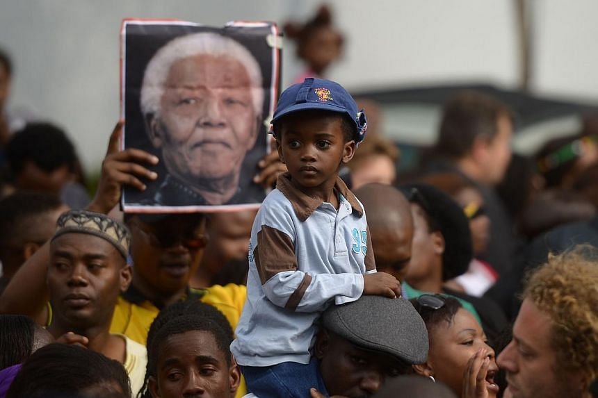 People pay tribute to South African former president Nelson Mandela outside his home in Houghton, Johannesburg, on Dec 8, 2013, three days after his death. -- PHOTO: AFP