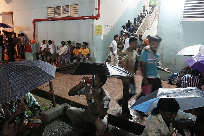 Crowds drinking  at the stairway and spilling out to the void deck at a block of flats in Chander Road in Little India.