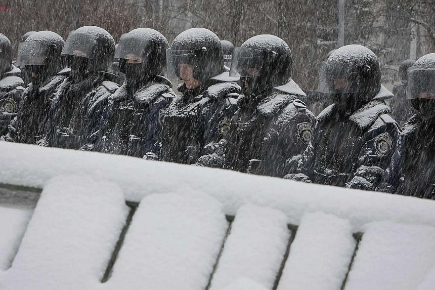 Interior ministry personnel stand guard during snowfall on a street in Kiev on Monday, Dec 9, 2013.Ukrainian riot police on Monday took up position near Kiev's city hall, which is occupied by pro-Europe protesters demonstrating against a govern