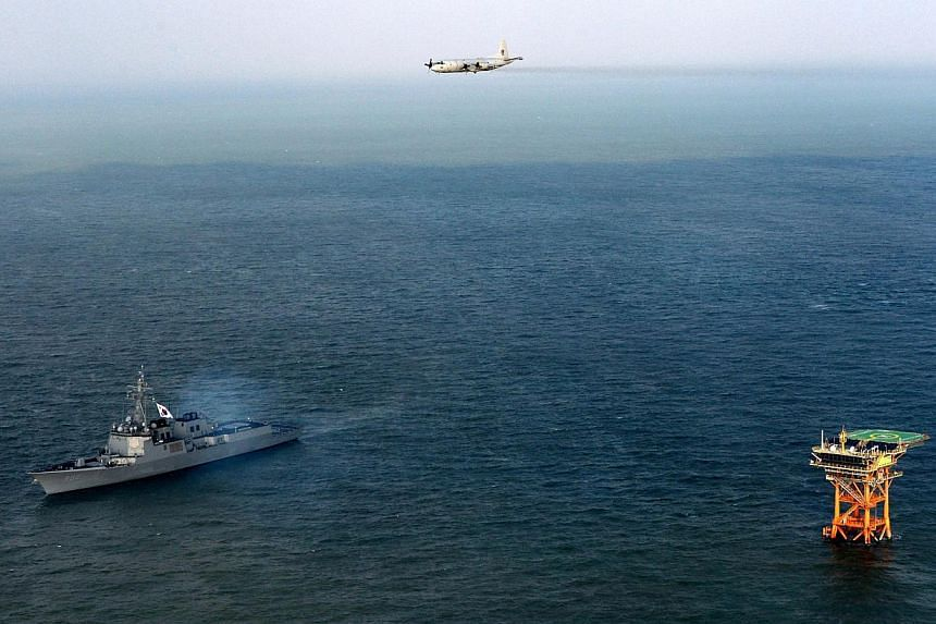"This picture taken on Dec 2, 2013, shows the South Korean Navy patrol-aircraft P-3C (top) and South Korean Aegis DDG-992 (left) during defence operations near Ieodo Ocean Research Station. China expressed ""regret"" on Monday, Dec 9, 2013, at Sout"