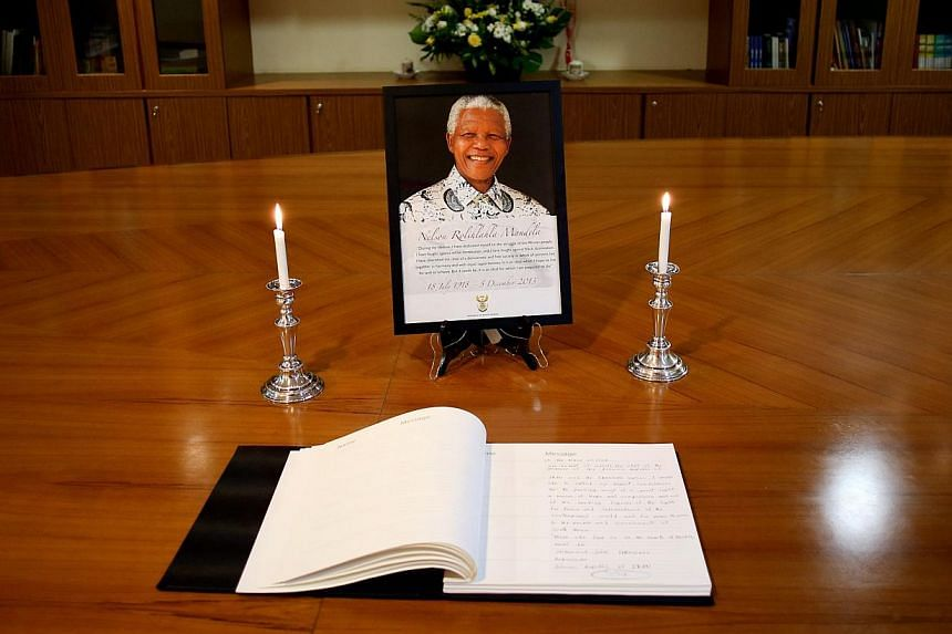 The condolence book is seen in front of a photograph of the late former South African president Nelson Mandela at the South African High Commission in Kuala Lumpur on Monday, Dec 9, 2013. -- PHOTO: AFP