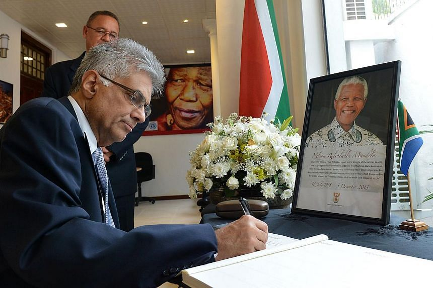 Sri Lanka's opposition leader Ranil Wickremesinghe signs a condolence book at the South African High Commission in Colombo on Monday, Dec 9, 2013. -- PHOTO: AFP