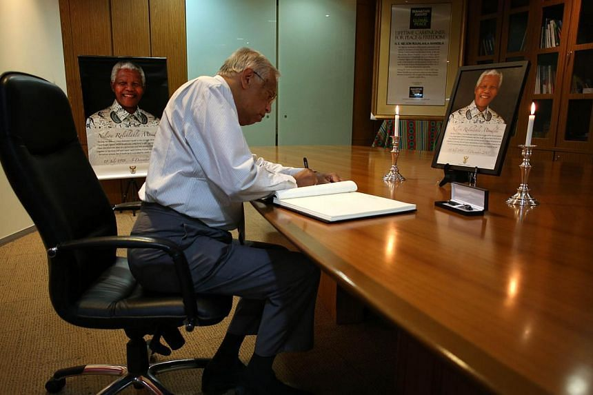 A diplomat writes messages of condolence in front of a photograph of the late former South African president Nelson Mandela at the South African High Commission in Kuala Lumpur on Monday, Dec 9, 2013. -- PHOTO: AFP