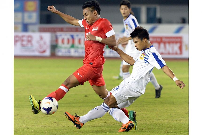 Singapore's Shahfiq Ghani (left) in a duel during their football match against Laos in the 27th SEA Games in Naypyitaw, Myanmar on Sunday, Dec 8, 2013. Singapore football fans can now follow the SEA Games football action live on terrestrial tele