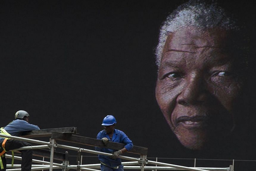 An image of Nelson Mandela is displayed on a digital screen as workers on scaffolding construct a stage ahead of Mr Mandela's national memorial service at First National Bank (FNB) Stadium in Johannesburg on Monday, Dec 9, 2013.President Barack