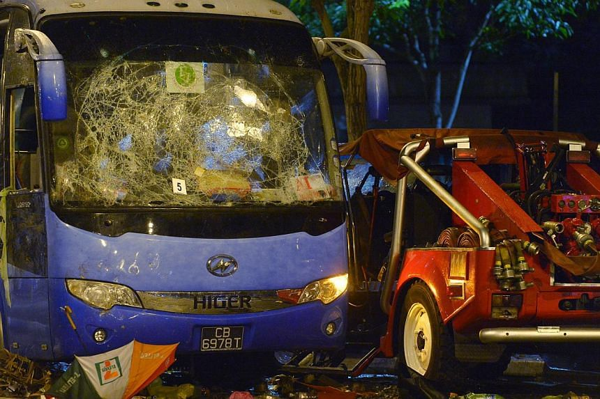The wrecked tour bus and red rhino is seen at the scene of the riot that took place in Little India, Race Course Road and Buffalo Road on Monday, Dec 9, 2013. The driver involved in the Little India accident on Sunday night that sparked a riot h