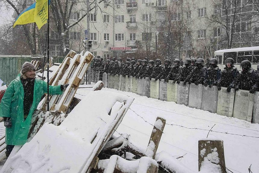 Interior ministry personnel stand guard opposite a barricade erected by supporters of EU integration during snowfall on a street in Kiev on Monday, Dec 9, 2013. Hundreds of protesters blocked several main streets in the centre of Ukrainian capital Ki