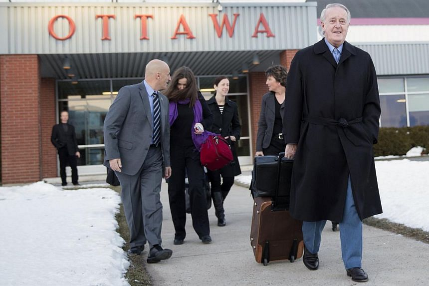 Canada's former Prime Minister Brian Mulroney (right) prepares to board Challenger for a trip to Johannesburg, South Africa to attend a public memorial for Mr Nelson Mandela, in Ottawa on Dec 8, 2013. More than 70 heads of state and government are ex