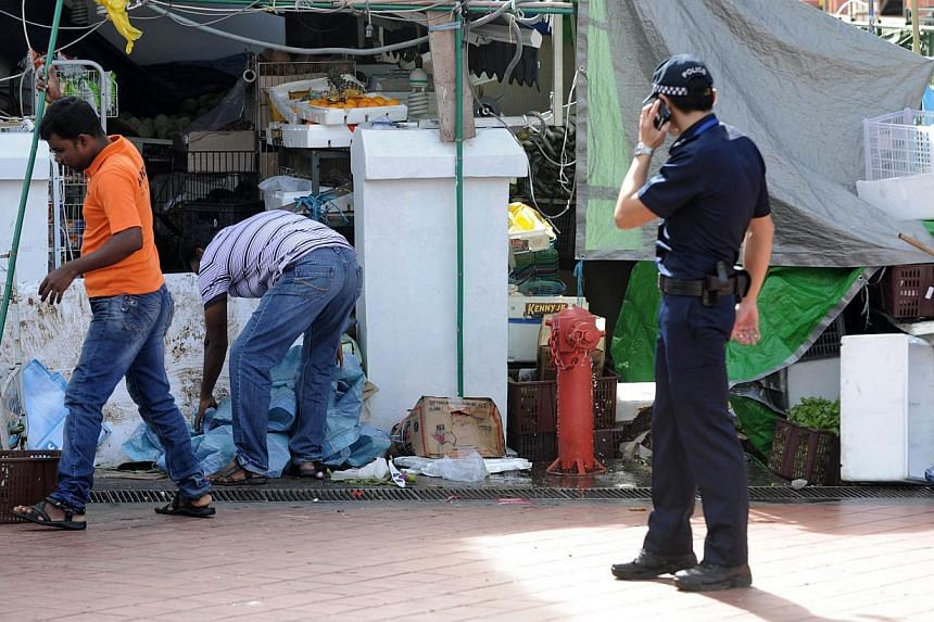 Two workers cleaning up a vegetables shop on Dec 9, 2013, next to where rioters went on a rampage in Little India the night before. Shop owners and residents affected by the riot were seen clearing up the debris from the violence, with most counting
