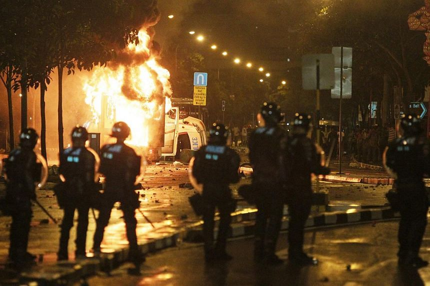 Members of SPF's Special Operation Command stand in front of a burning ambulance during a riot involving almost 400 people broke out in Little India along Race Course Road on Dec 8, 2013. Twenty-seven men from South Asia were arrested in connection w