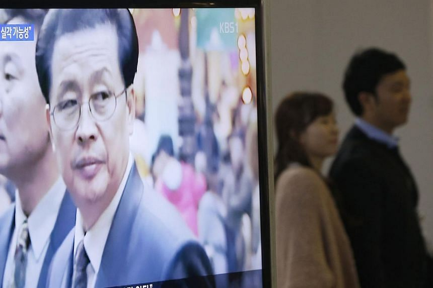 A couple walks past a television showing a report on Jang Song Thaek, North Korean leaders' uncle, at a railway station in Seoul on Dec 3, 2013. North Korea confirmed on Monday that leader Kim Jong Un's uncle Jang Song Thaek was removed from off