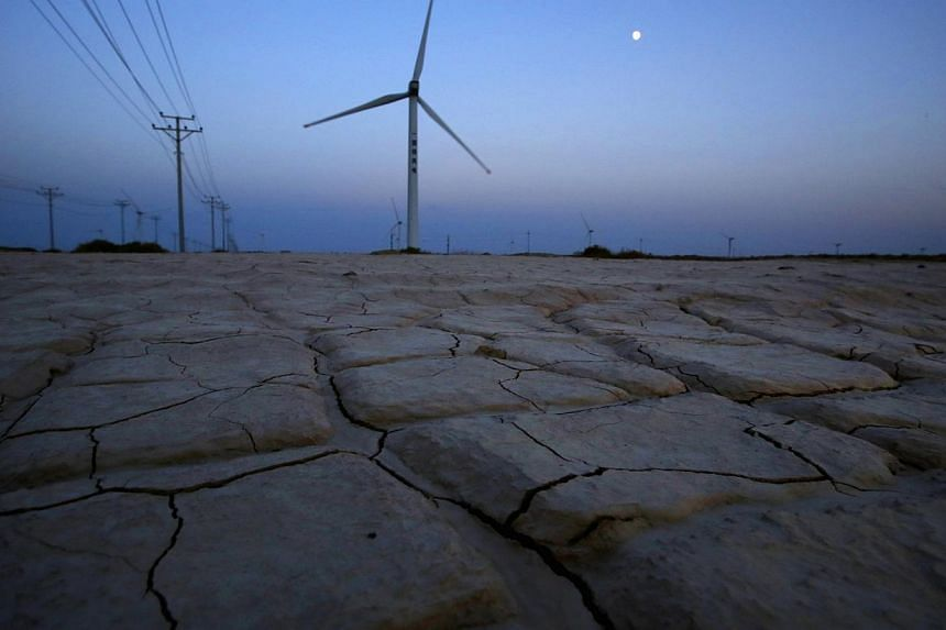 Cracked earth marks a dried-up area near a wind turbine used to generate electricity at a wind farm in Guazhou, 950km north-west of Lanzhou, Gansu Province on Sept 15, 2013. China is poorly prepared to tackle the impact of climate change that present