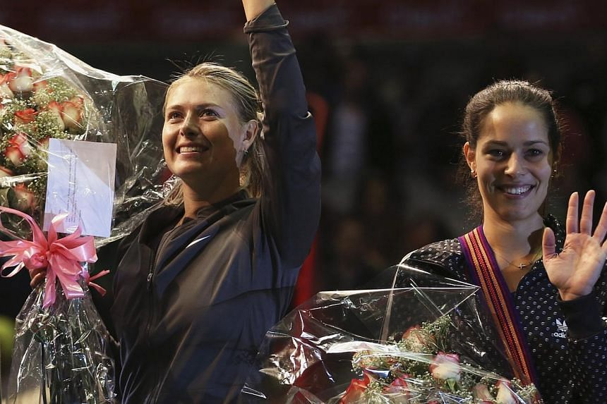 """Russia's Maria Sharapova (left) and Serbia's Ana Ivanovic wave to the fans after their exhibition match in Bogota, on Dec 6, 2013. Maria Sharapova described her return after a four-month injury absence as a """"baby step"""" forward in her recovery.-"""