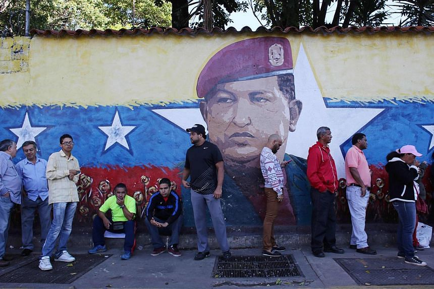 Voters waiting in line to enter a polling station in front of a wall painting depicting late president Hugo Chavez during municipal elections in Caracas, Venezuela, on Sunday, Dec 8, 2013. The elections will be a a gauge of their judgment on the gove
