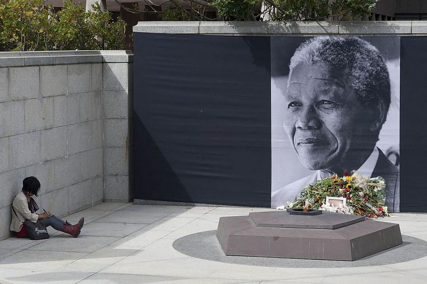 A woman sits next to a giant picture of late South African president Nelson Mandela set in front of the South African Parliament on Dec 9, 2013, in Cape Town, on the eve of a memorial ceremony for the anti-apartheid icon who died on Dec 5, 2013.&nbsp