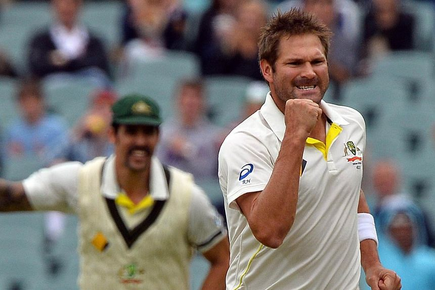 Australia's paceman Ryan Harris (right) celebrating during the last day of the second Ashes cricket Test match in Adelaide on Dec 9, 2013. Australia's media revelled in their team's humbling of hapless England on Tuesday, writing off the tourists ahe