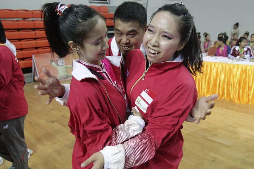 Singapore's Vera Tan (left) and Valerie Wee (right) rejoice after winning gold in women's duilian (barehand) event for wushu in the 27th SEA Games in Wunna Theikdi Indoor Stadium, Naypyidaw, Myanmar, on Dec 10, 2013.  -- ST PHOTO: KEVIN LIM