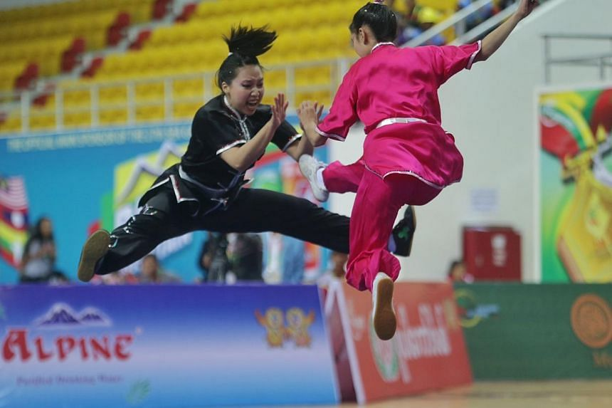 Singapore's Vera Tan (right) and Valerie Wee en route to winning gold in women's duilian (barehand) event for wushu in the 27th SEA Games in Wunna Theikdi Indoor Stadium, Naypyidaw, Myanmar, on Dec 10, 2013. -- ST PHOTO: KEVIN LIM