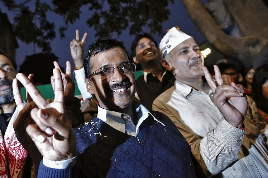 Arvind Kejriwal (centre), leader of the newly formed Aam Aadmi (Common Man) Party, gestures before addressing the media after his election win against Delhi's chief minister Sheila Dikshit, at his party office in New Delhi Dec 8, 2013. -- PHOTO: REUT