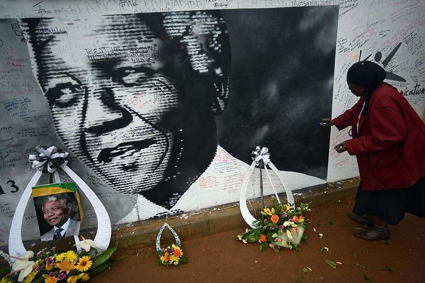 A woman writes a message on a wall of late South African President Nelson Mandela's house in Soweto on Dec 10, 2013.