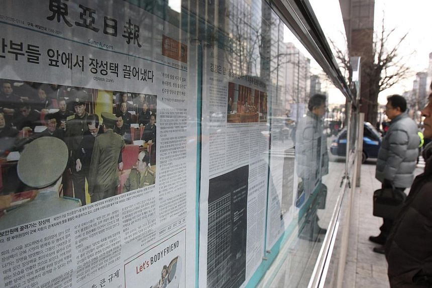 A man reads a newspaper reporting North Korea confirmed downfall of Jang Song Thaek, uncle of North Korean leader Kim Jong Un, displayed on a street in Seoul, South Korea, Tuesday, Dec. 10, 2013. South Korean President Park Geun Hye called Kim's purg